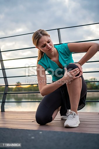 istock Young Woman Suffered a Knee Injury During Morning Exercise 1199486804