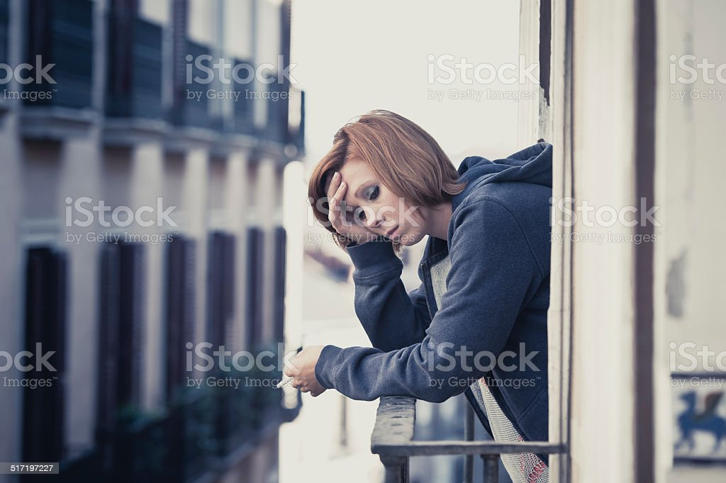 young woman suffering depression and stress outdoors at the balcony stock photo