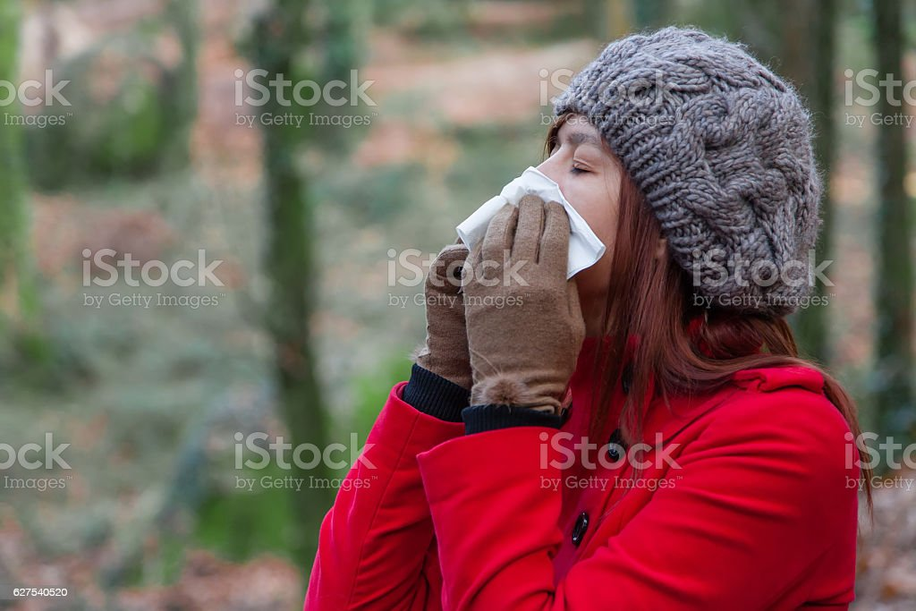 Young woman suffering from a cold, flu or allergies blowing her nose...