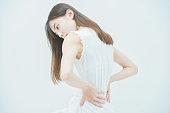 背中の痛みに苦しむ若い女性
