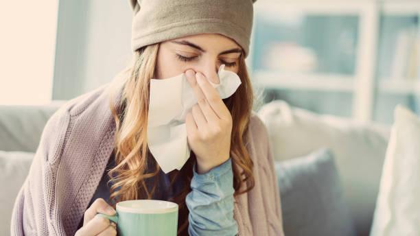 junge frau leidet unter erkältung - erkältung und grippe stock-fotos und bilder