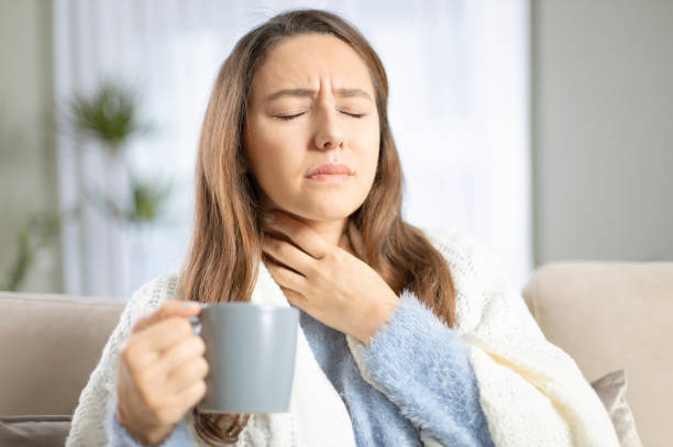 Young woman suffering from cold Young woman touching painful neck, sore throat for flu, cold and infection throat stock pictures, royalty-free photos & images