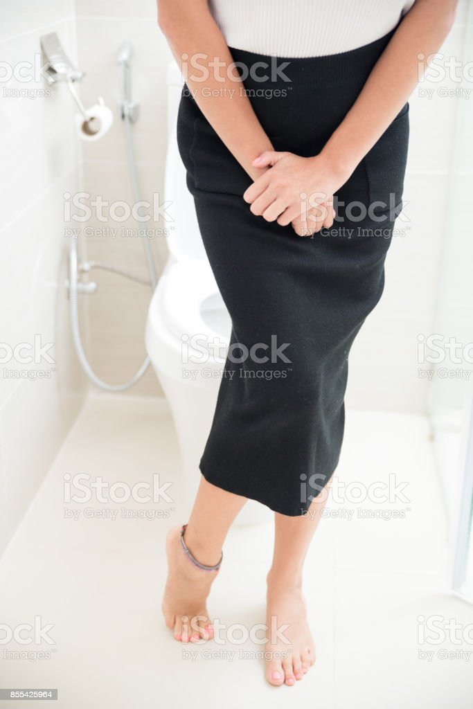 Young woman suffering from cystitis in toilet stock photo