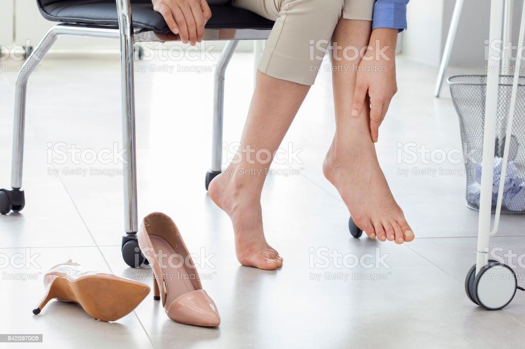 Young woman suffering from foot pain in office стоковое фото