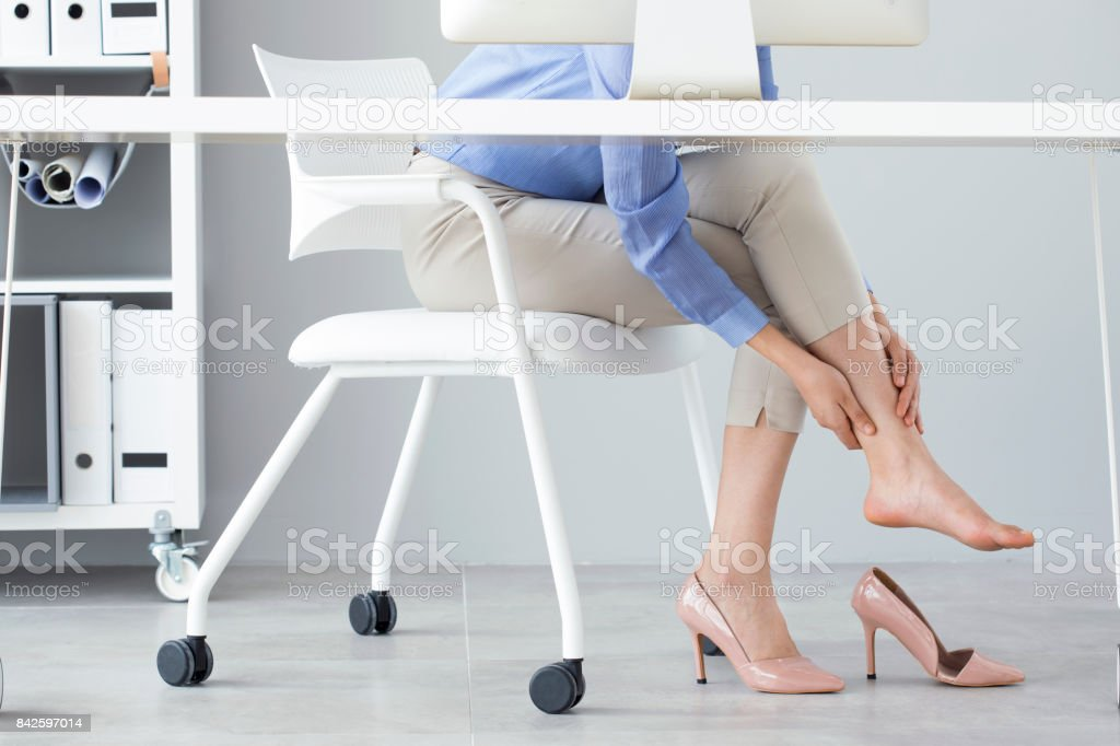 Young woman suffering from foot pain in office stock photo