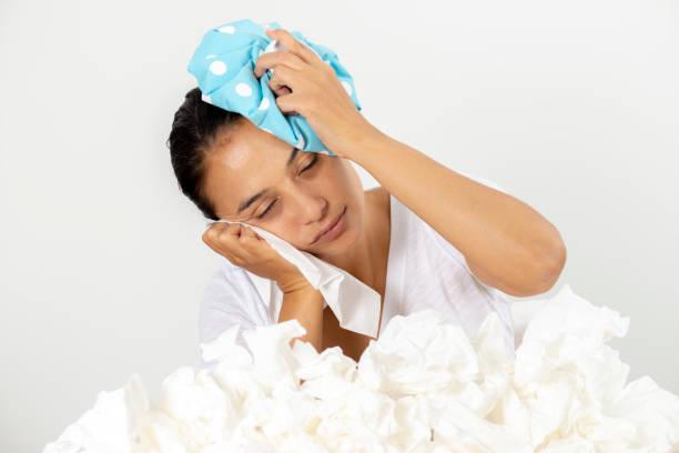 ung kvinna som lider av huvudvärk - mature woman fever on white bildbanksfoton och bilder
