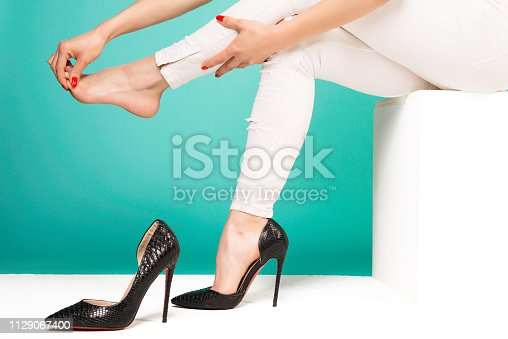 istock Young woman suffering from leg pain massaging toes because of uncomfortable shoes 1129067400