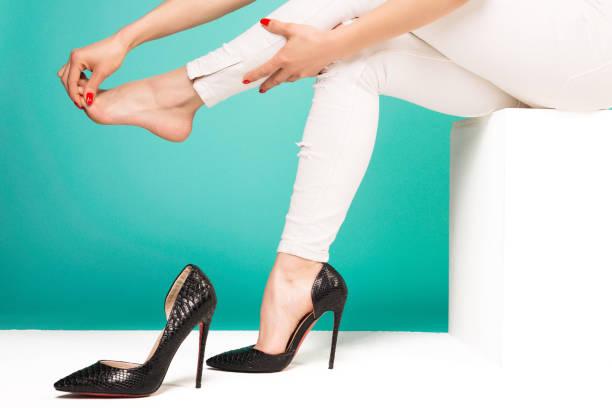 jonge vrouw die lijden aan pijn in het been masseren tenen vanwege ongemakkelijk schoenen - hoge hakken stockfoto's en -beelden