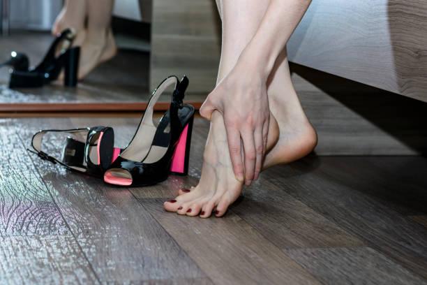 Junge Frau mit Beine Schmerzen wegen der unbequemen Schuhen mit hohen Absätzen – Foto
