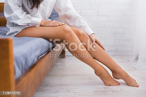 Leg pain or calf muscle, woman suffering in bed in morning, copy space