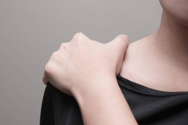 Young woman suffering from pain in shoulder,  Pain in the human body on a gray background stock photo