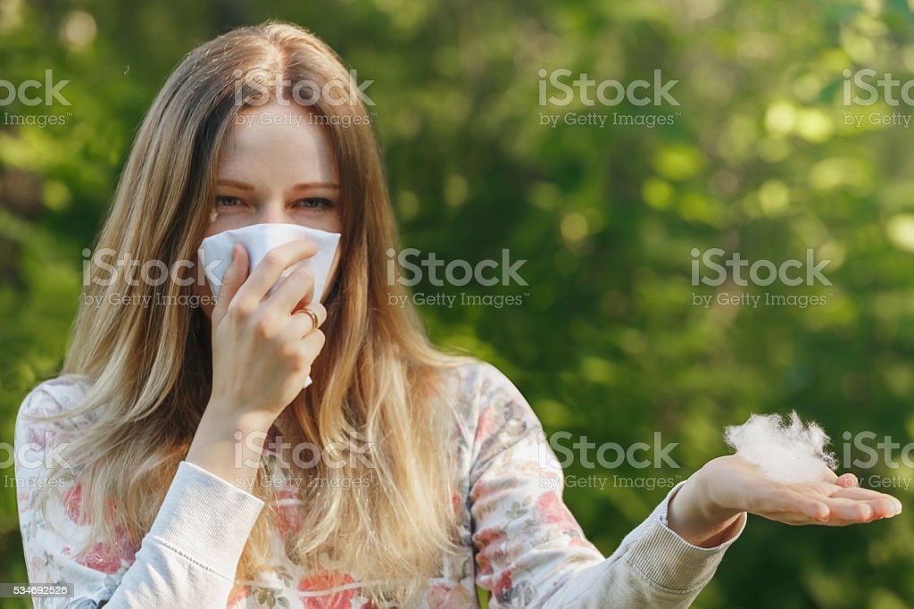 young woman suffering spring pollen allergy. Sneezing into a white...