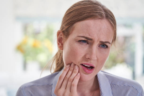 Young Woman Suffering With Toothache Touching Jaw Young Woman Suffering With Toothache Touching Jaw toothache stock pictures, royalty-free photos & images