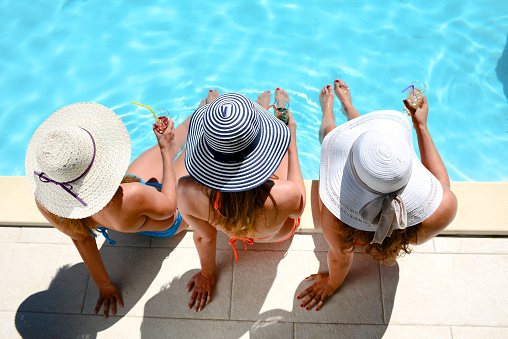 young woman sun hat sitting poolside resort pool summer holiday