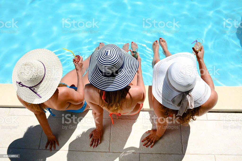 young woman sun hat sitting poolside resort pool summer holiday stock photo