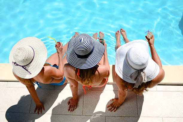 young woman sun hat sitting poolside resort pool summer holiday – Foto
