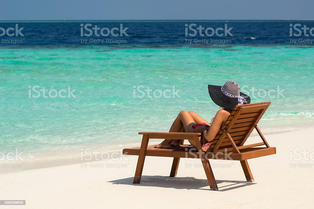 Young woman sunbathing on lounger at tropical beach royalty-free stock photo