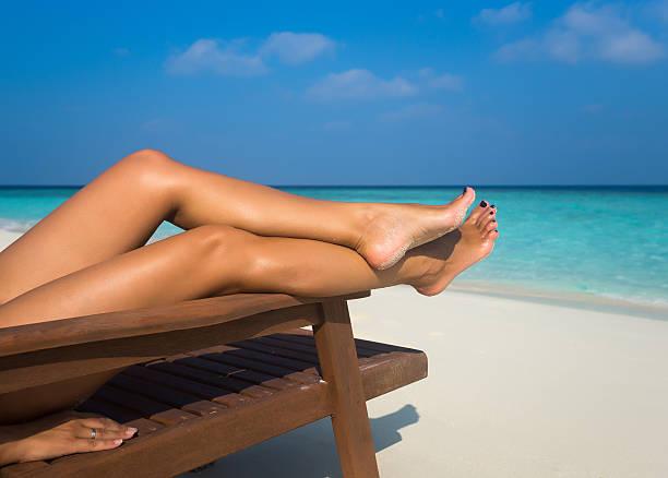 young woman sunbathing on lounger. legs. - gebruind stockfoto's en -beelden