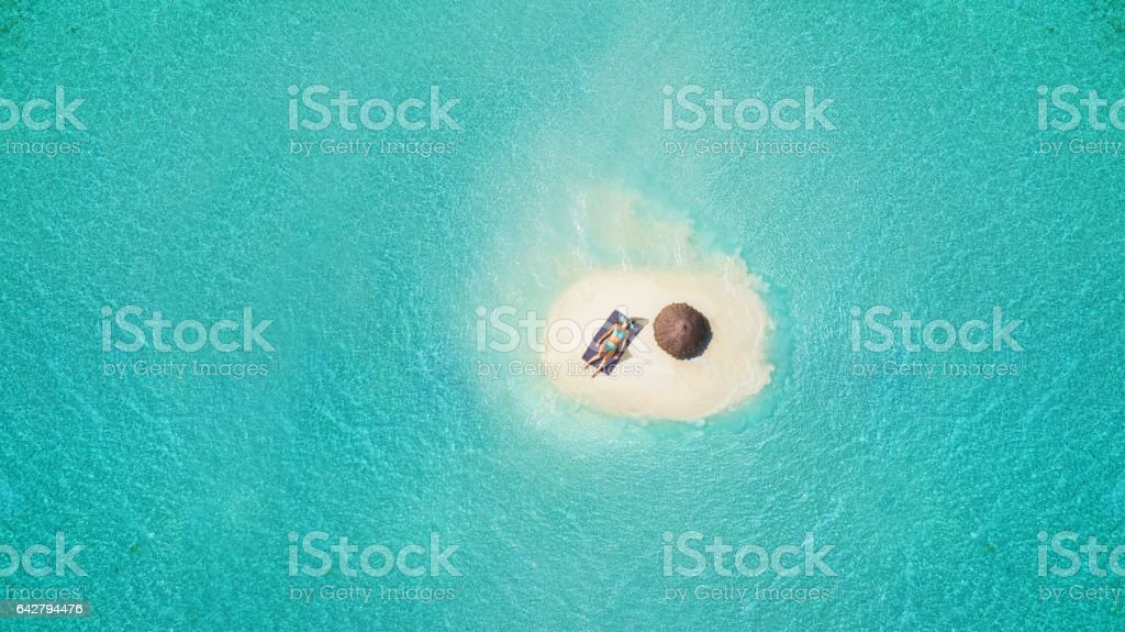 Young woman sunbathing on tiny sandy island stock photo