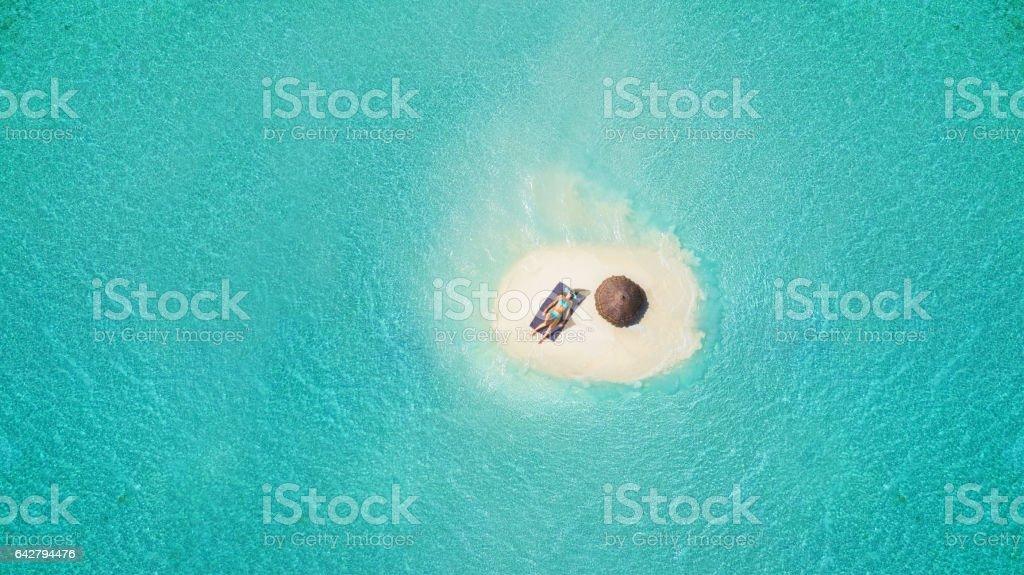 Young woman sunbathing on tiny sandy island stok fotoğrafı