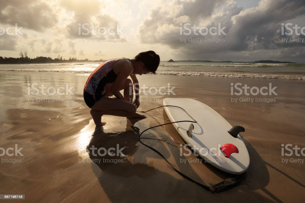 young woman surfer ready to surf on a beach - Photo