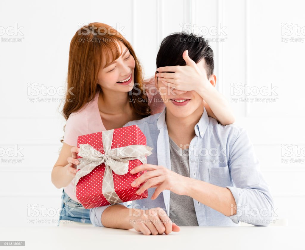 young woman surprises his boyfriend with present at home stock photo