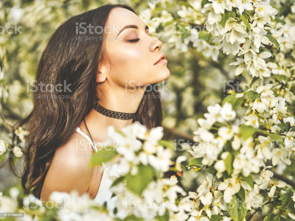 Young woman surrounded by flowers of apple-tree stock photo
