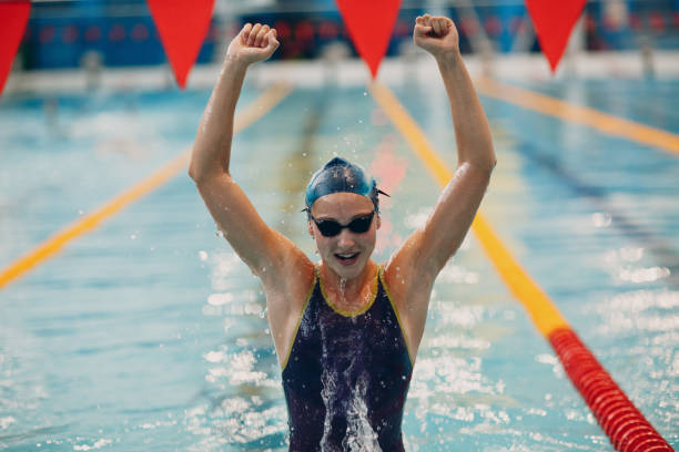 young woman swimmer portrait joy rejoices in victory in swimming competitions in swimming pool - swim arms imagens e fotografias de stock