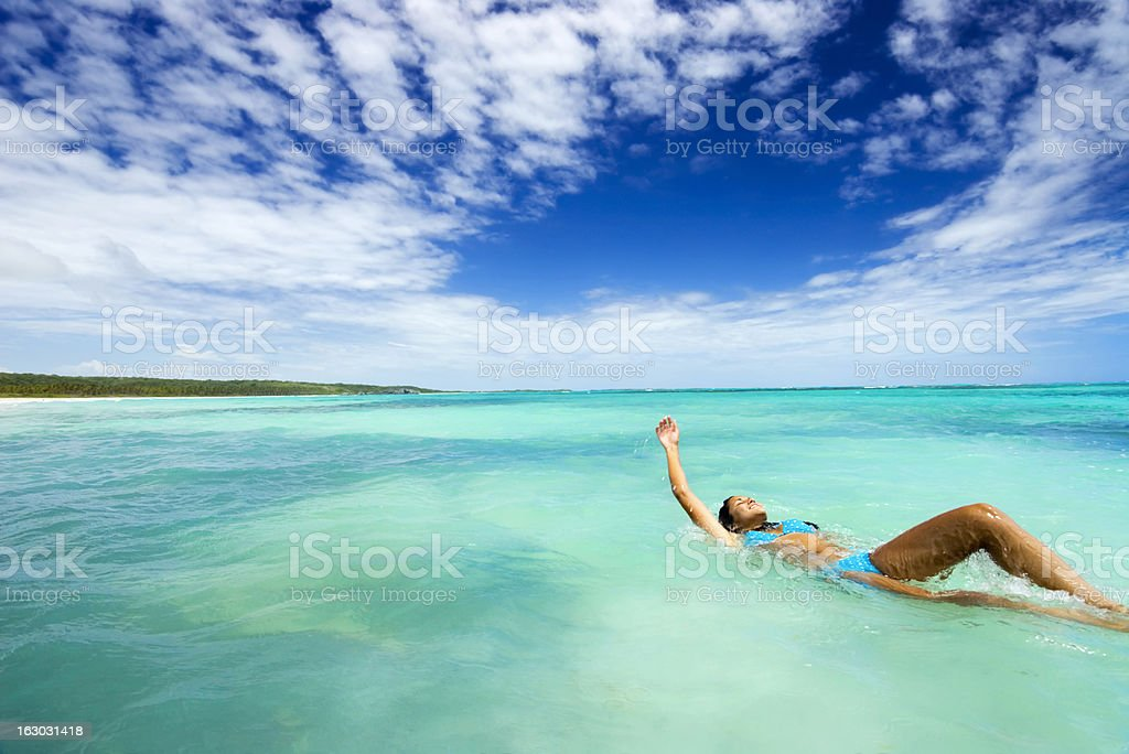 Young Woman Swimming Backwards in Tropical Ocean stock photo
