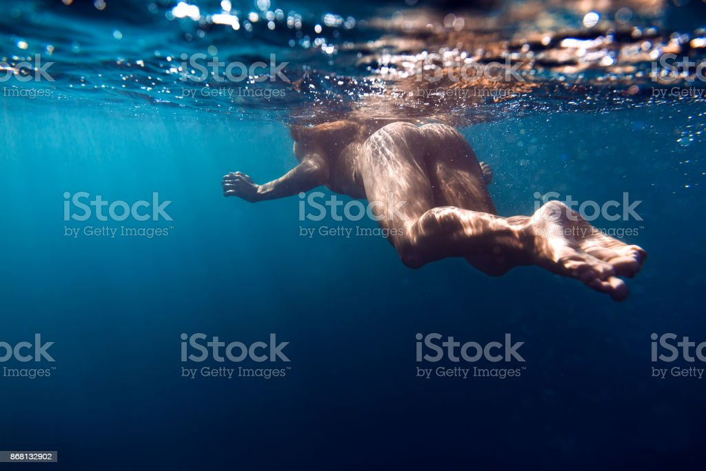 Young woman swimming in ocean, snorkeling underwater view stock photo