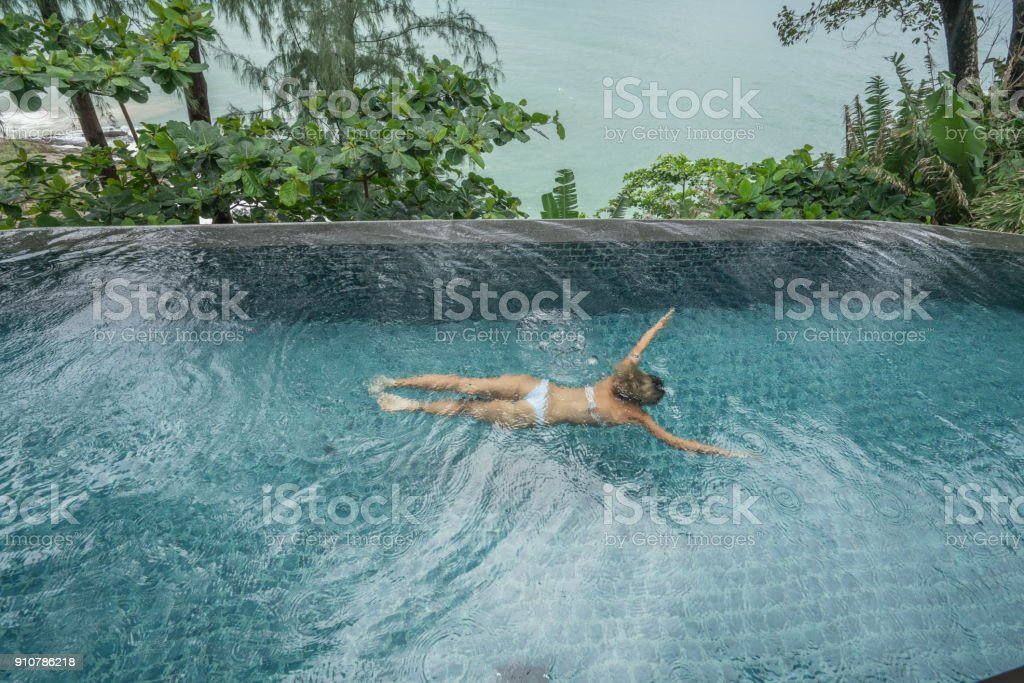 Young woman in private pool villa by the ocean, luxury vacations...