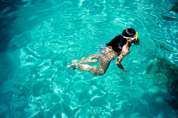 Young Woman Swimming in the Ocean a young woman snorkeling in the Mediterranean sea. middle aged women in bikinis stock pictures, royalty-free photos & images