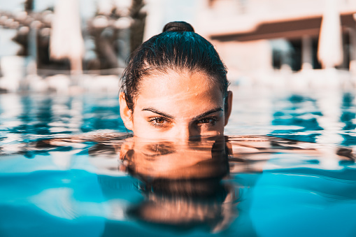 Photo of young woman in the pool , close up portrait