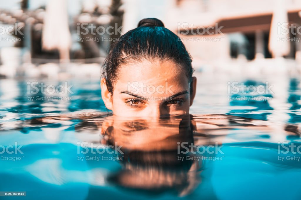 Young woman swimming in the pool stock photo