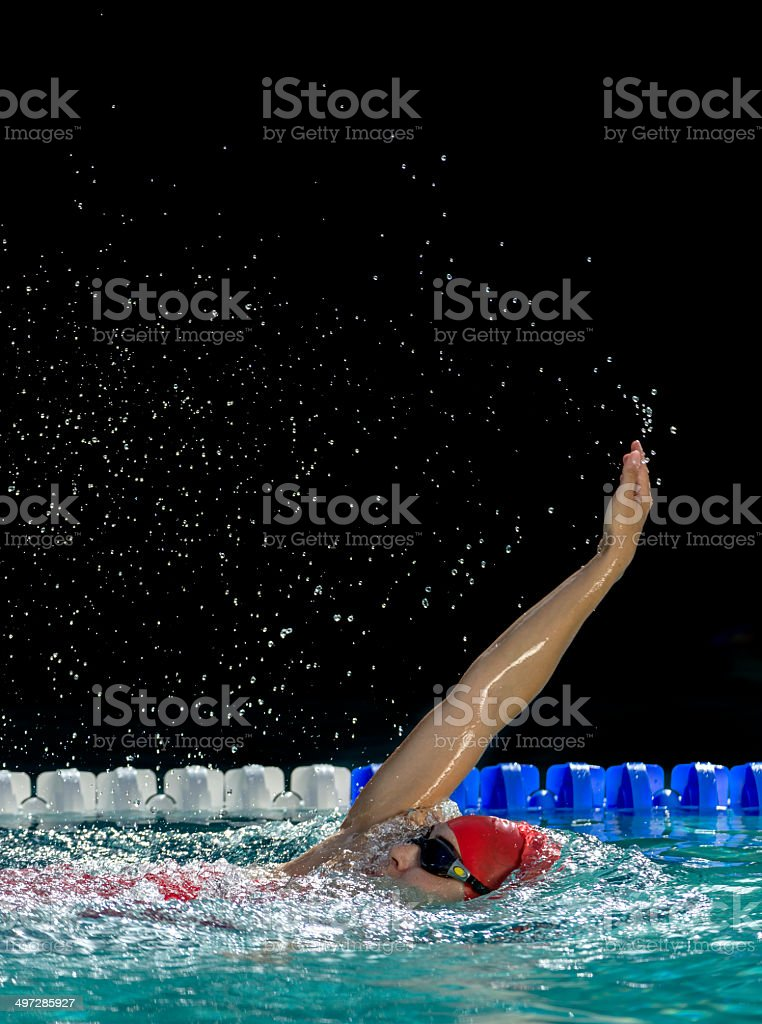 Young woman swimming in a race, back stroke.