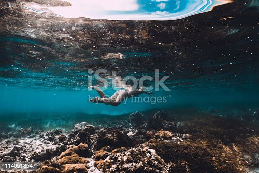 istock Young woman swimming underwater in the tropical blue ocean 1140513547