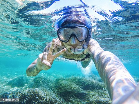 istock Young woman swimming with mask snorkeling 518841278