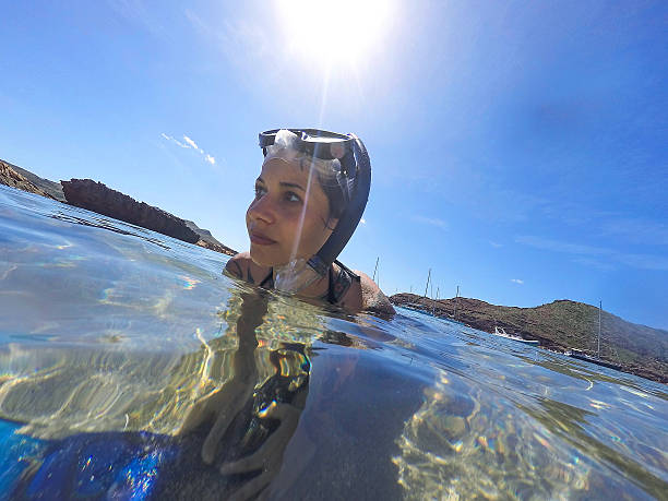 Young woman swimming with mask snorkeling stock photo