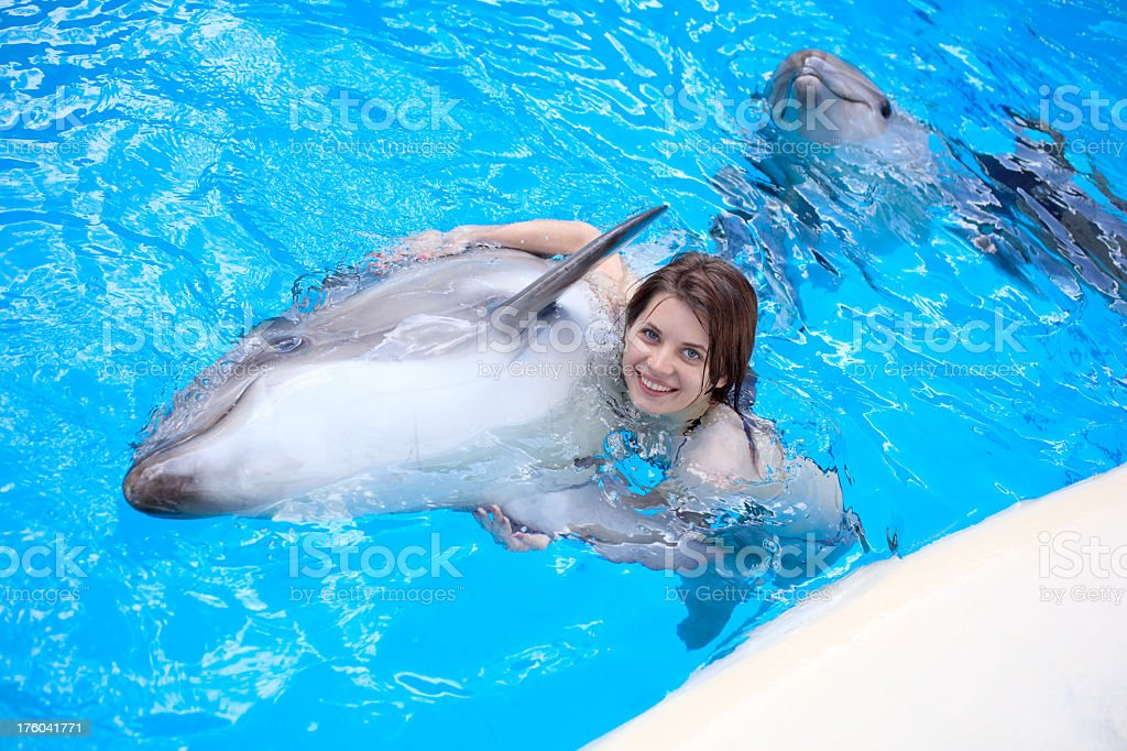 Young Woman Swims With A Dolphin In The Pool Stock Photo