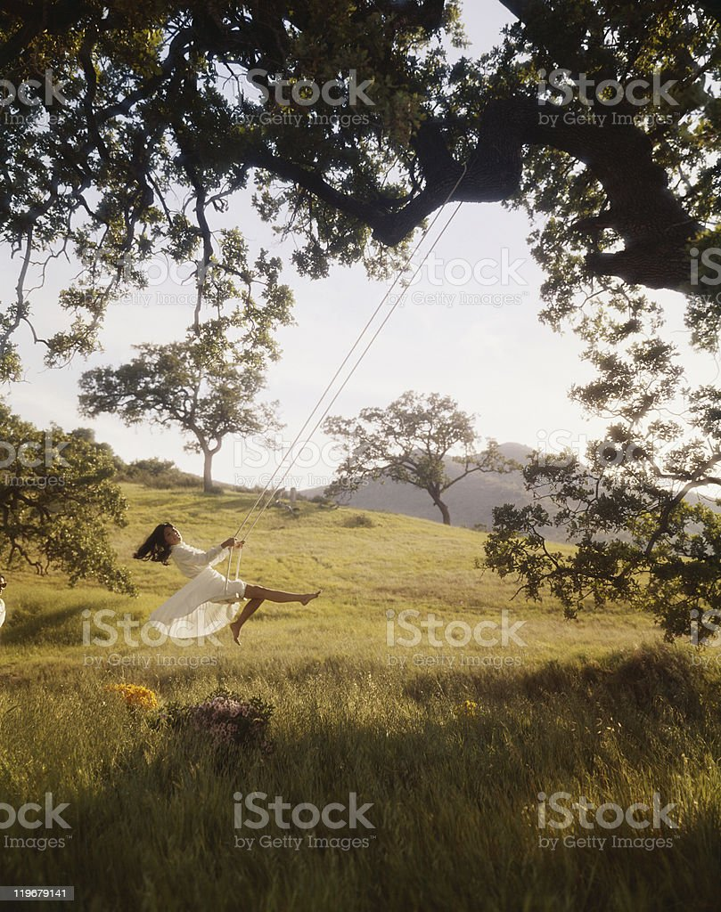 Young woman swinging on rope swing tied on tree royalty-free stock photo