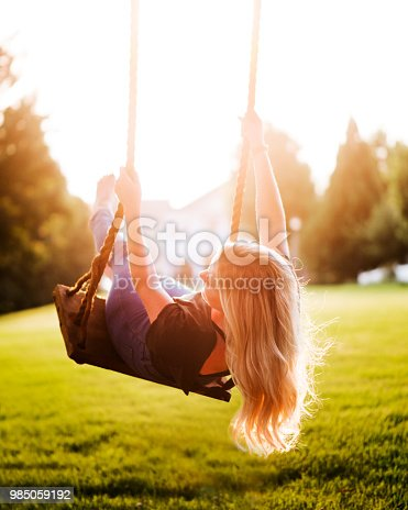 Young woman swinging on swing in park at sunset.