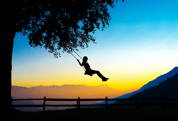 Young Woman Swinging silhouette stock photo