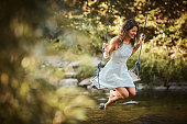 Young woman swings over stream
