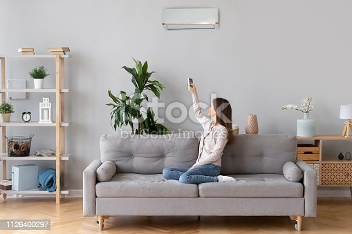 istock Young woman switching on air conditioner sitting on couch 1126400297