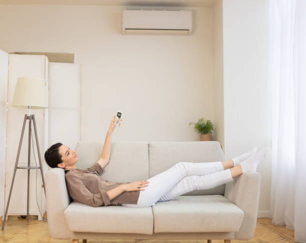 young woman switching on air conditioning at her house - telecomando background foto e immagini stock