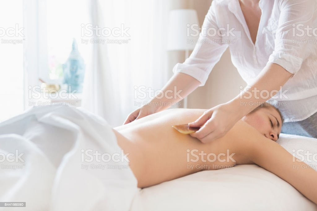 Young woman take back treatment at health spa stock photo