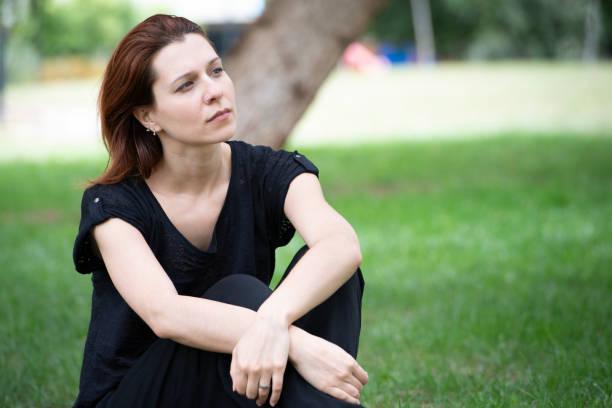 Jovem mulher faz uma pausa no parque - foto de acervo
