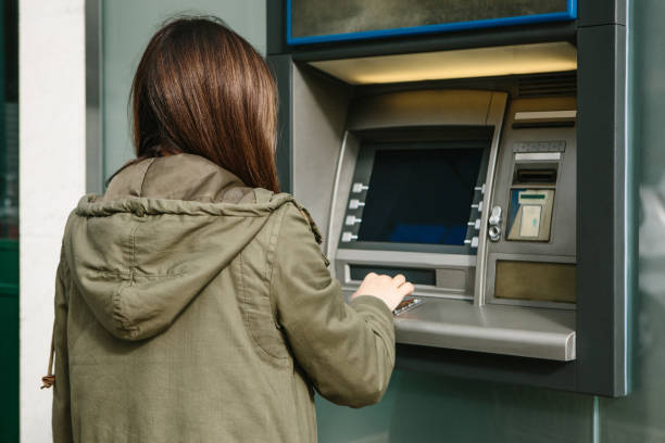 a young woman takes money from an atm. grabs a card from the atm. finance, credit card, withdrawal of money. - orthographic symbol stock photos and pictures