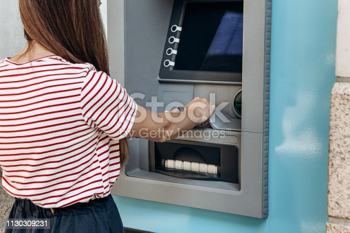 945598452istockphoto A young woman takes money from an ATM. 1130309231