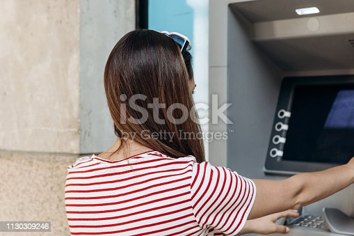 945598452istockphoto A young woman takes money from an ATM. 1130309246